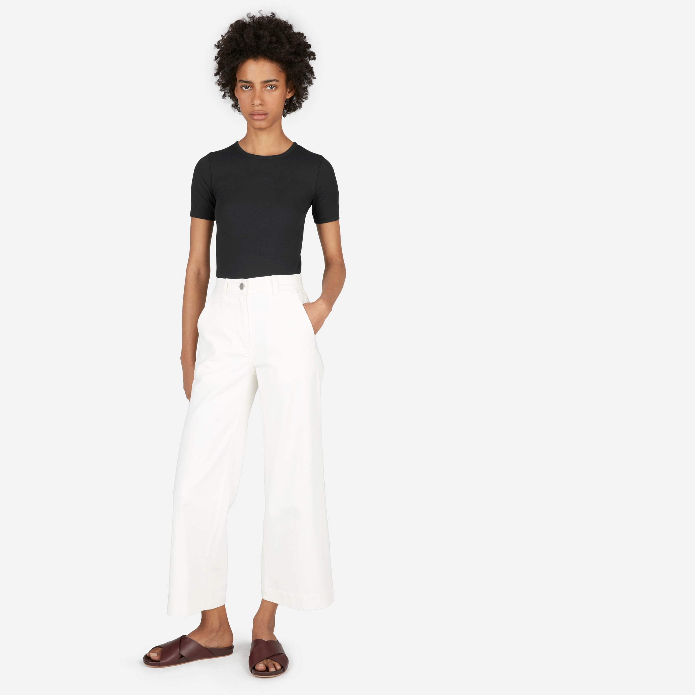 A woman in an black Everlane t-shirt and white pants stands against a white background.