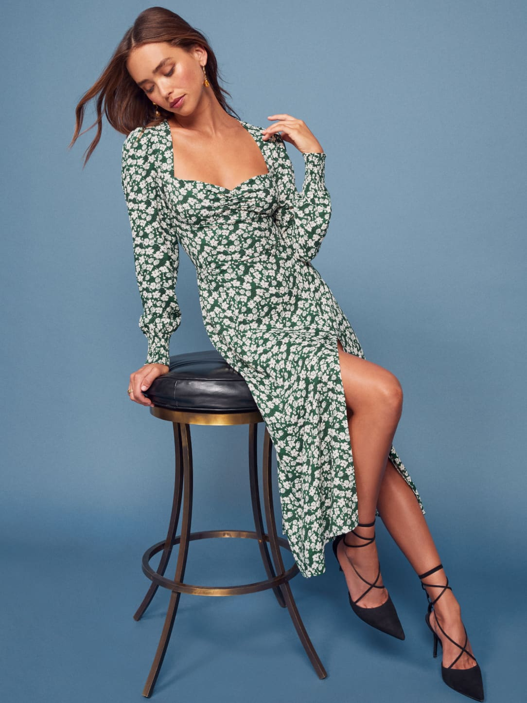 A woman in a green floral dress from Reformation sits on a stool against a dark blue background.