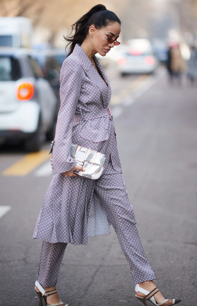 Tamara Kalinic crosses the street in a patterned suit, sunglasses, and high heels while carrying a silver clutch.