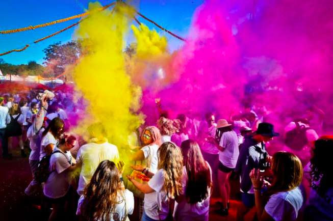 A crowd of young people stand in clouds of colored dust at the Splendour In The Grass music festival.