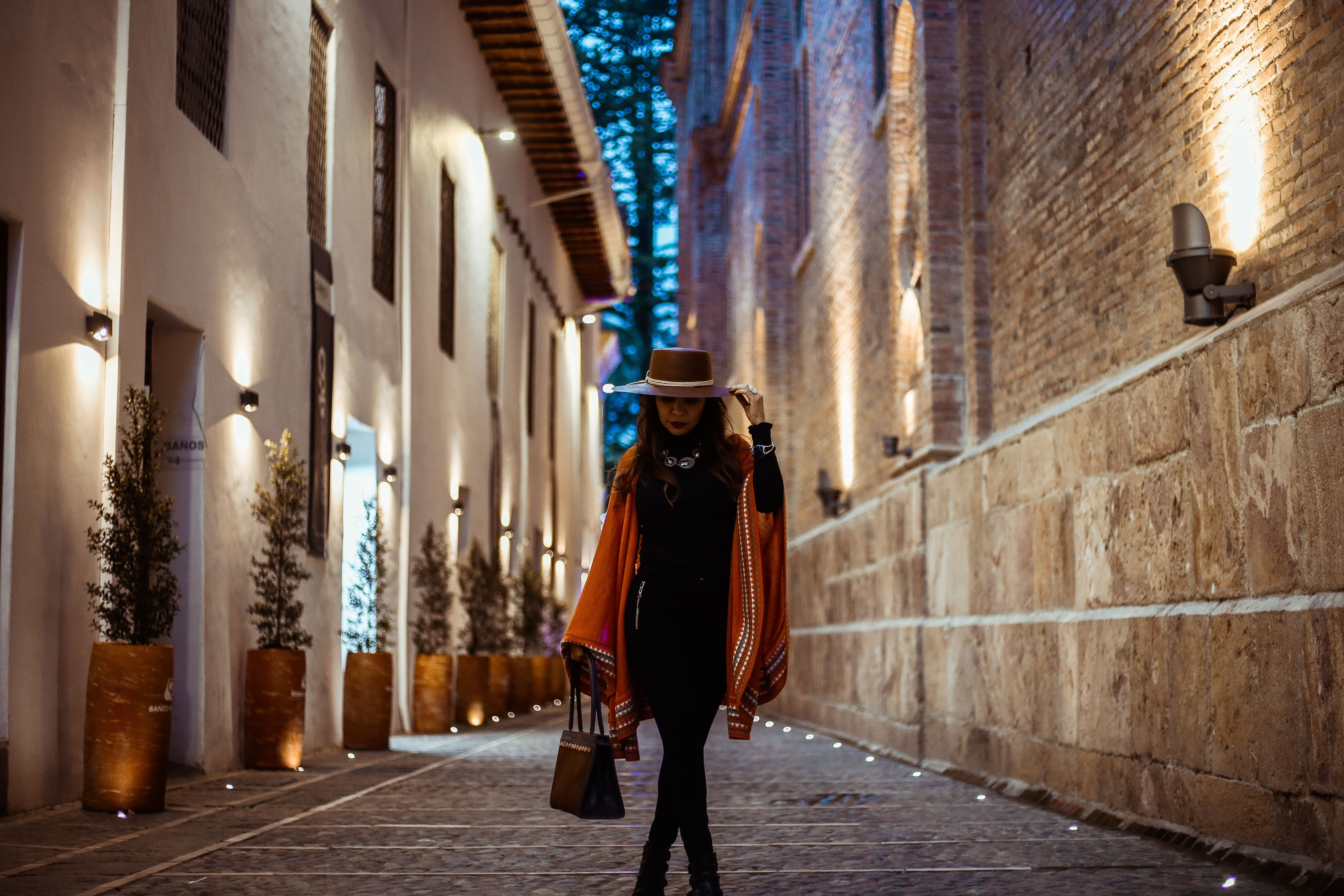 Woman standing in cobblestone alley in black dress and brown hat.
