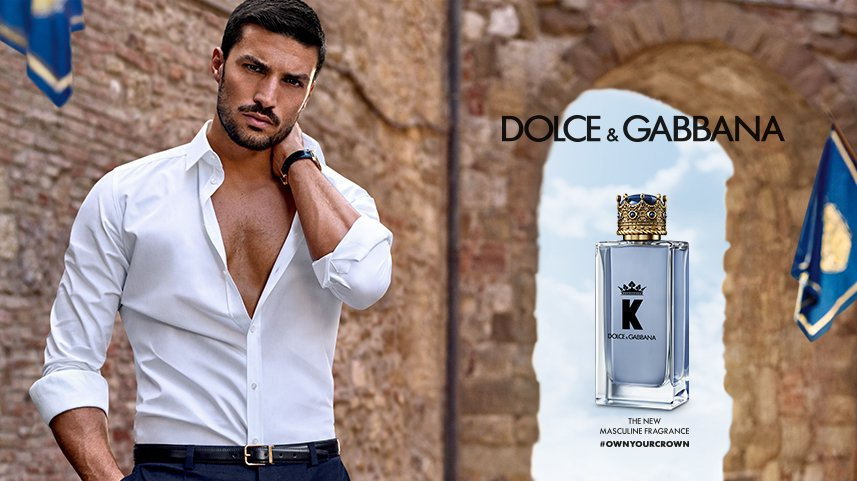 Italian influencer Mariano Di Vaio poses against a castle wall in a white shirt next to Dolce & Gabbana Beauty's K Eau de Toilette.