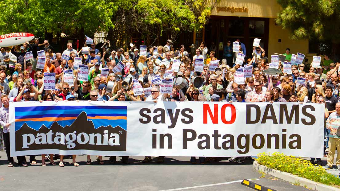 """Patagonia employees protest with a sign that reads """"Patagonia says no dams in Patagonia."""""""