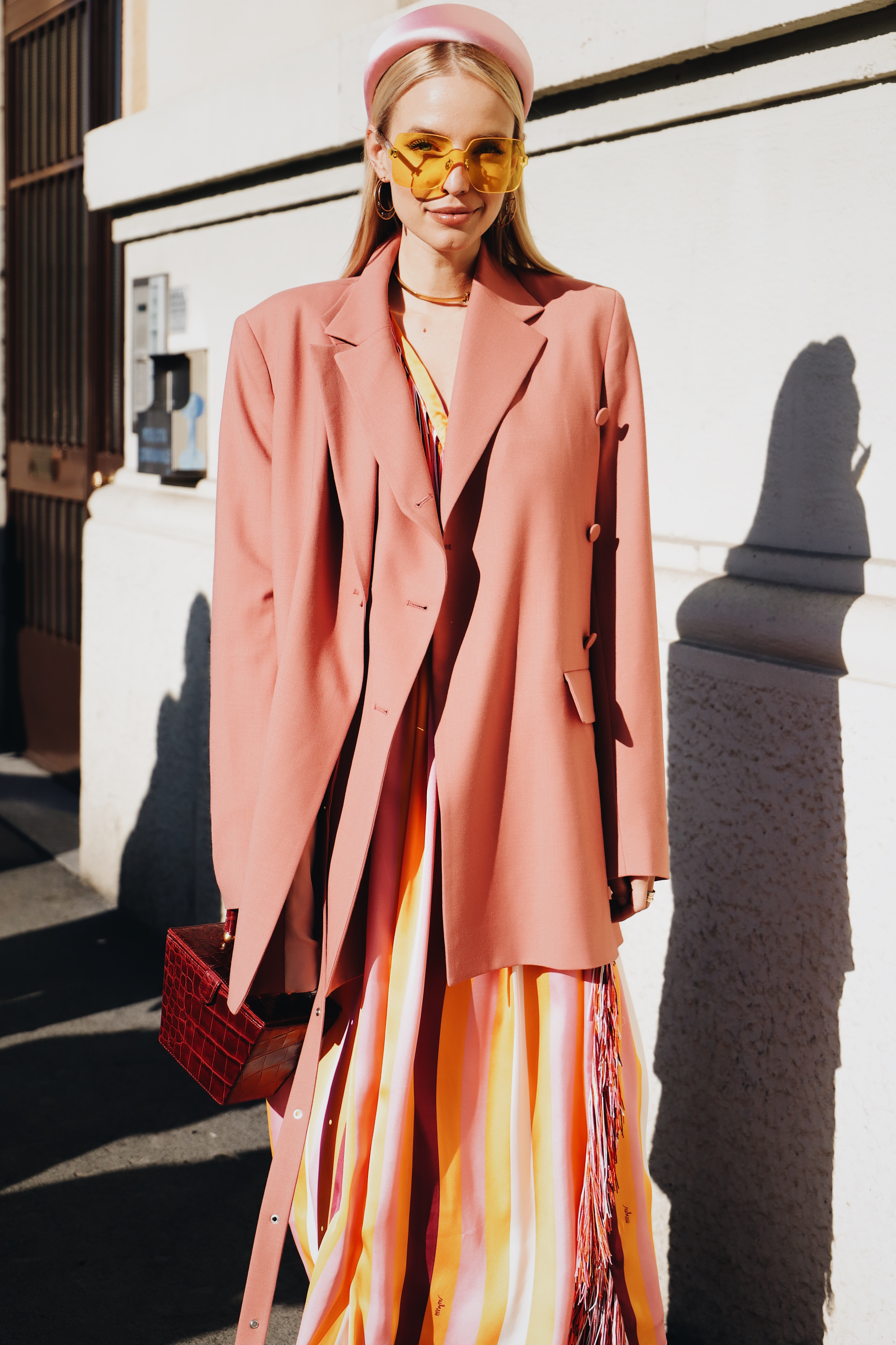Leonie Hanne wearing pink hat and coat with orange sunglasses and red purse.